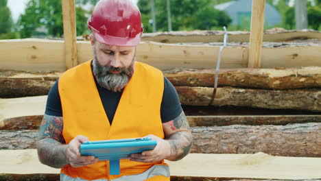 A-bearded-builder-in-a-helmet-uses-a-smartphone-2