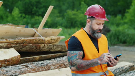 A-bearded-builder-in-a-helmet-uses-a-smartphone-3