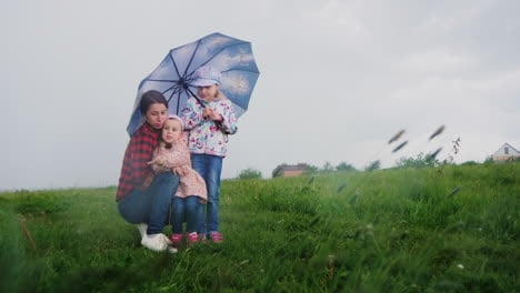 A-woman-with-children-hides-under-an-umbrella-from-the-rain