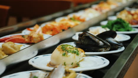 Seafood-plates-move-on-conveyor-belt-at-All-Inclusive-Restaurant