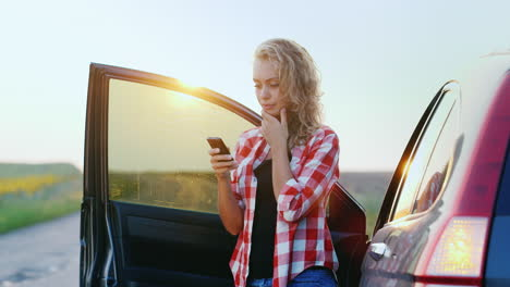 A-woman-is-talking-on-the-phone-standing-by-a-car-1