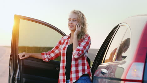 A-woman-is-talking-on-the-phone-standing-by-a-car-2