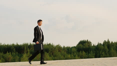 A-businessman-with-a-case-in-his-hand-walks-along-a-sandy-beach