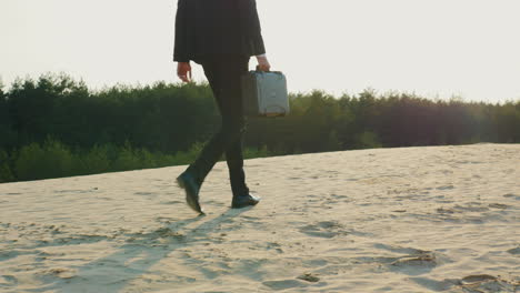 A-businessman-with-a-case-in-his-hand-walks-along-a-sandy-beach-1