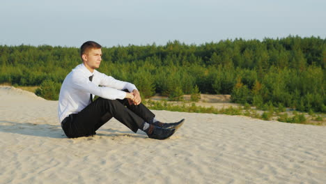 A-young-businessman-in-a-suit-sits-on-the-sand