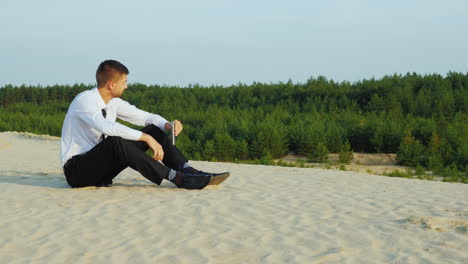 A-businessman-drinks-alcohol-and-sits-on-the-sand