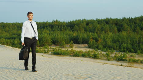 A-businessman-with-a-case-in-his-hand-walks-along-a-sandy-beach-2