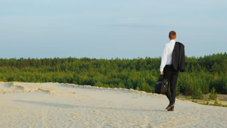 A-businessman-with-a-case-in-his-hand-walks-along-a-sandy-beach-3