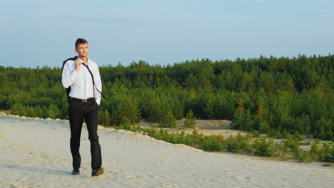 A-satisfied-and-happy-businessman-walks-on-the-sand