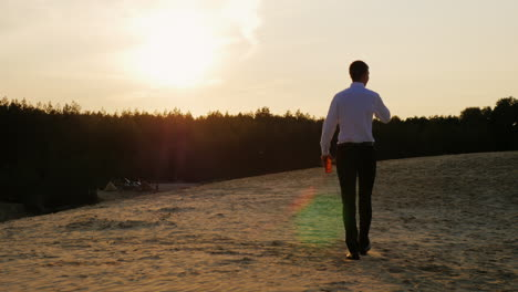A-businessman-with-a-bottle-of-alcohol-walks-forward-on-the-sand