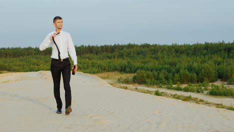 A-businessman-with-a-bottle-of-alcohol-walks-forward-on-the-sand-1