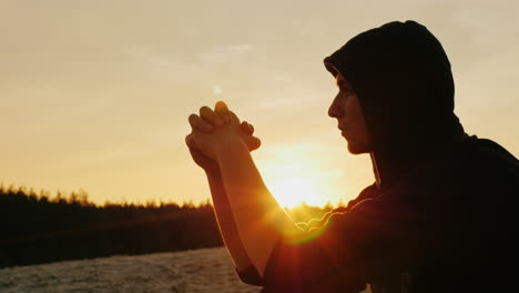 A-young-man-in-a-hood-prays-at-sunset
