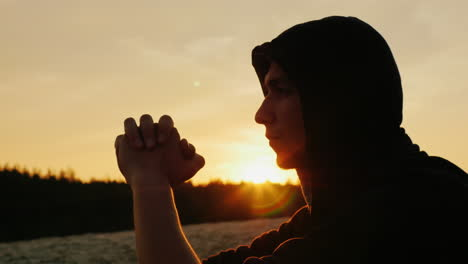 A-young-man-in-a-hood-prays-at-sunset-1