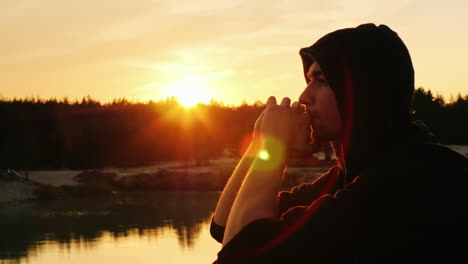 A-young-man-in-a-hood-prays-at-sunset-2