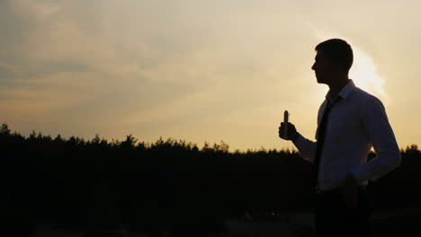 Silhouette-of-a-businessman-drinking-alcohol-at-sunset