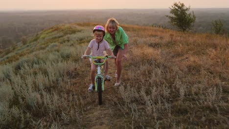 Mother-teaches-her-daughter-to-ride-a-bicycle
