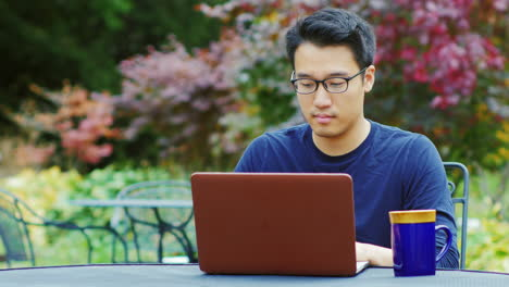 A-Young-Asian-Man-Works-With-A-Laptop