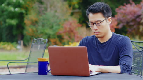 A-Young-Asian-Man-Works-With-A-Laptop-2