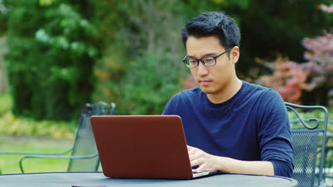 A-Young-Asian-Man-Works-With-A-Laptop-4
