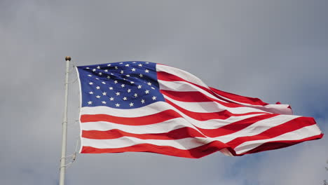Large-Us-Flag-On-A-Background-Of-Gray-Sky-Beautifully-Illuminated-By-The-Sun