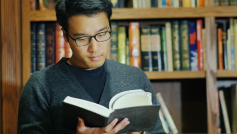 Good-Looking-Asian-Man-In-Glasses-Reading-A-Book-In-The-Library