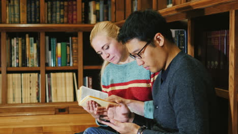 Korean-Man-And-Caucasian-Woman-Look-At-A-Book-In-The-Library-Communicate-Using-A-Tablet