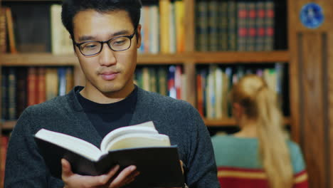 Good-Looking-Asian-Man-In-Glasses-Reading-A-Book-In-The-Library-1