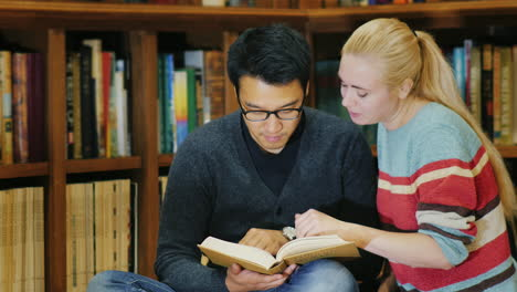 Asian-Man-With-Glasses-And-Caucasian-Women-Standing-Together-Watching-The-Book-In-The-Library