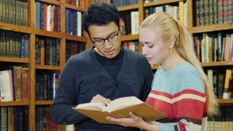 Asian-Man-With-Glasses-And-Caucasian-Women-Standing-Together-Watching-The-Book-In-The-Library-1
