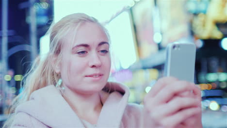 A-Woman-Tourist-Takes-Pictures-Of-The-Phone-On-The-Famous-Time-Square-In-New-York-City