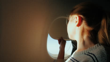 A-Female-Passenger-Looks-Out-The-Window-Of-The-Plane-To-The-City-Below