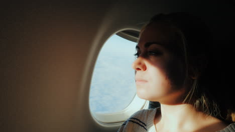 A-Female-Passenger-Looks-Out-The-Window-Of-The-Plane-To-The-City-Below-1