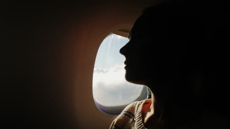 A-Female-Passenger-Looks-Out-The-Window-Of-The-Plane-To-The-City-Below-2