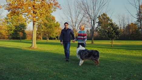 Young-Carefree-Couple-Walking-With-A-Dog-In-The-Park