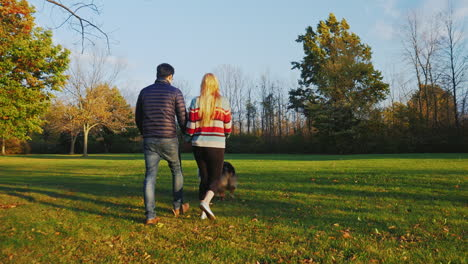 Young-Carefree-Couple-Walking-With-A-Dog-In-The-Park-1