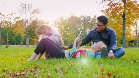 Young-Multi-Ethnic-Couple-Relaxing-In-The-Park-With-Their-Dog-2