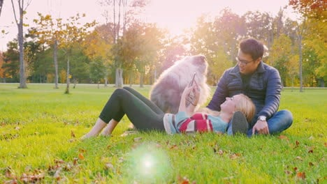 Young-Multi-Ethnic-Couple-Relaxing-In-The-Park-With-Their-Dog-3