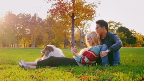 Young-Multi-Ethnic-Couple-Relaxing-In-The-Park-With-Their-Dog-4