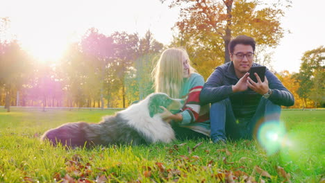 Young-Multi-Ethnic-Couple-Relaxing-In-The-Park-With-Their-Dog-5
