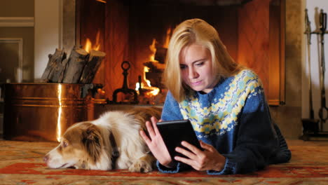 Caucasian-Young-Woman-Lying-By-The-Fireplace-Use-The-Tablet
