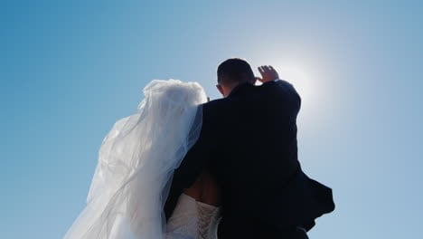 The-Bride-And-Groom-Looking-Up-Closing-The-Sun-With-His-Hand