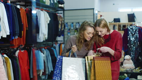 Satisfied-Customers-Look-Into-Their-Shopping-Bags-At-The-Clothing-Store