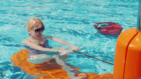 Young-Woman-Exercising-In-The-Pool-Outdoors-In-The-Resort