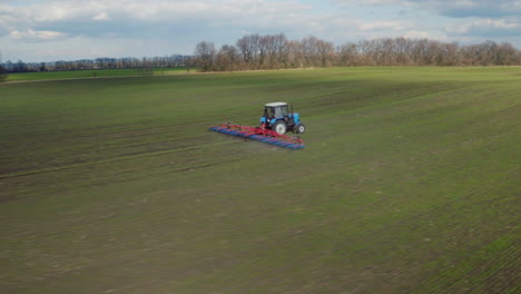 Drone-Shot-Over-Tractor-With-Harrow-System-Plowing-Ground-On-Cultivated-Farm-Field
