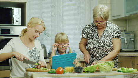 Grandmother-Mother-And-Granddaughter-Cook-Together-A-Salad-In-The-Kitchen