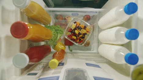 Midnight-Snack-View-From-Inside-The-Refrigerator---Women-s-Hands-Take-Sweets-From-A-Plate