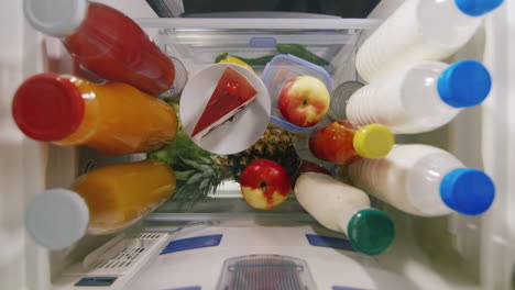 A-Woman-s-Hand-Chooses-Between-An-Apple-And-A-Cake-View-From-Inside-The-Refrigerator