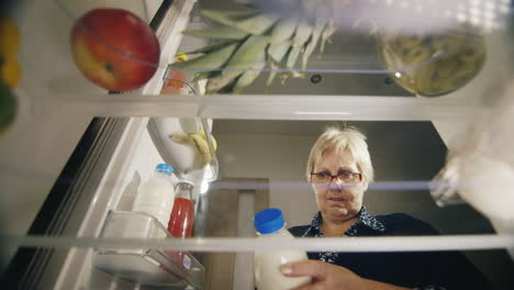 An-Senior-Woman-Takes-A-Bottle-Of-Milk-From-The-Refrigerator-Checks-The-Shelf-Life-Of-The-Product