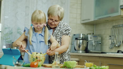 A-6-Year-Old-Girl-And-Her-Grandmother-Make-A-Salad-In-Kitchen