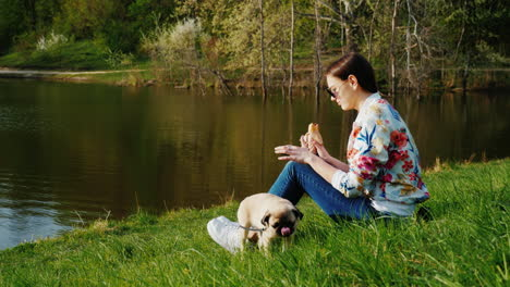 A-Woman-Sits-On-A-Lawn-Near-A-Lake-And-Eats-Fast-Food-Next-To-A-Dog
